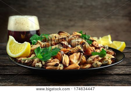 Seafood. Steamed Musseles appetizer with sprinkle of parsley and lemon juce served on black plate with glass of dark beer.