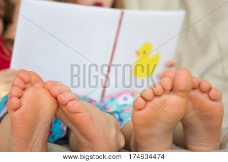 Two barefoot children reading a story in bed