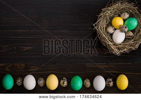Easter eggs in nest on a black background. Still life. Top view. Copy space