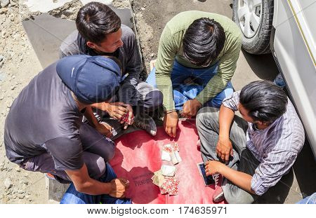 Ladakh, India - July 10, 2016: Taxi drivers play cards wile waiting for their passengers