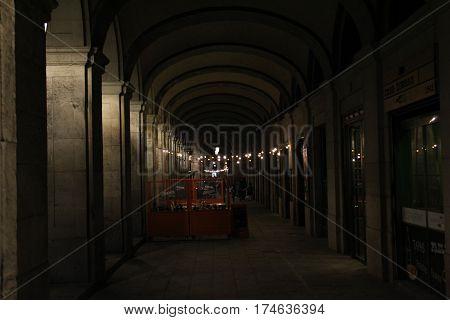 Fotografía callejón oscuro con mesas de restaurante y luces