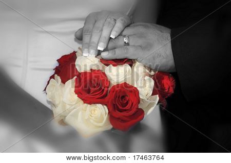 Couple With Their Wedding Rings and Hands On Top of Bridal Bouquet