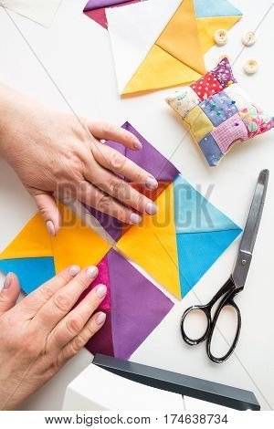 female hands coordinates geometric color fabric pieces for patchwork quilt. the process of creating scrappy blankets. top view. flat lay.