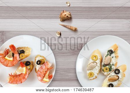 Tasty various italian sandwiches with seafood against rustic wooden background. Crostini with cheese king shrimps lemon sliced olives on white plate horizontal top view
