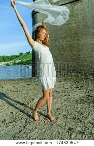 Young attractive woman in white dress and holding white scarf on river background