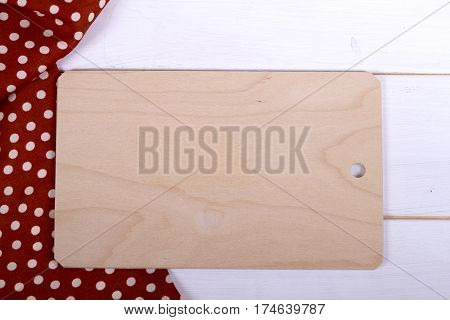 cutting board on a wooden table. with a kitchen towel polka, top view