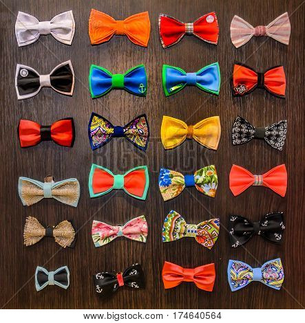 Сollection of bowtie which hangs on a wooden stand