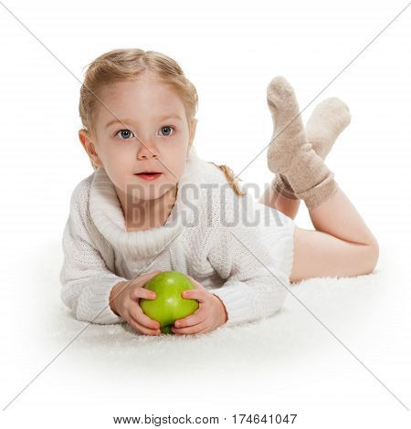 Three-year old girl with green apple lays on white lush carpet