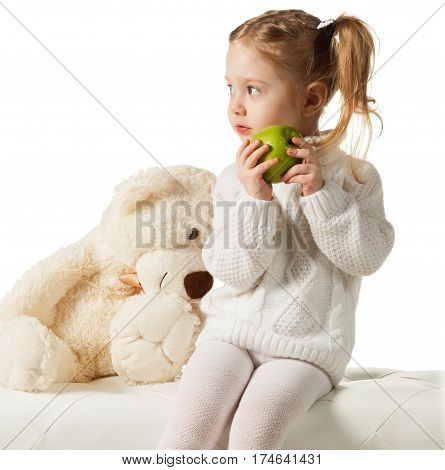 Three-year old girl in knitted sweater with green apple and teddy bear sitting on white leather pouf