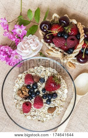 A bowl with hole grain flakes berries nuts and rose on sackcloth beige background. Healthy breakfast. Top view