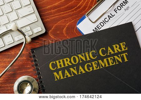 Book with title chronic care management on a table. Pain management concept.