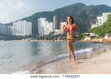 Fit young woman in bikini with sporty muscular sexy body jogging on seashore against mountains and high buildings. Slender female athlete training on beach doing cardio exercises