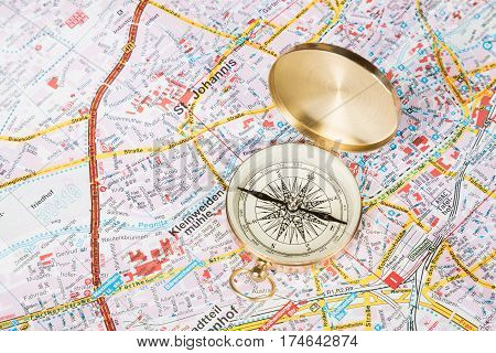 Travel concept. Compass close-up on city map with selective focus.