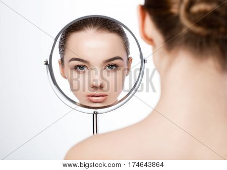 Beauty girl natural makeup looking in mirror reflection on white