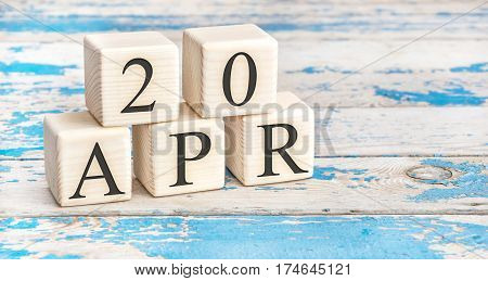April 20th. Wooden cubes with date of 20 April on old blue wooden background.