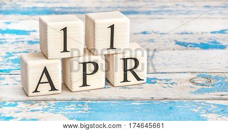 April 11Th. Wooden Cubes With Date Of 11 April  On Old Blue Wooden Background.