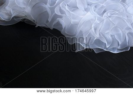 hem of a wedding dress on a black background. A beautiful background for invitation card