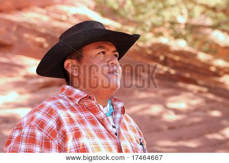 Mid adult male wearing cowboy hat. He is head and shoulders viewable and looking away from the camera. Horizontally framed shot.