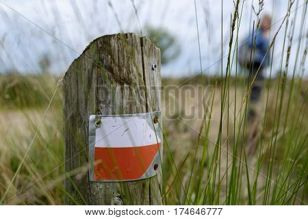 red white trail hiking pointer on a wooden pole in the grass