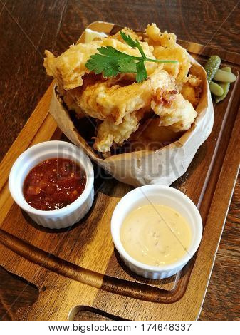 Stylist food deep fried calamari on paper bag with chilli sauce and mayonnaise or tartar sauce serve on the wooden tray with blur background top view