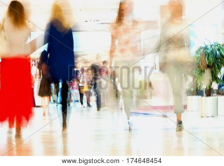 Abstract defocused motion blurred people, walking girlfriends in the shopping center. For background , backdrop, substrate, composition use.