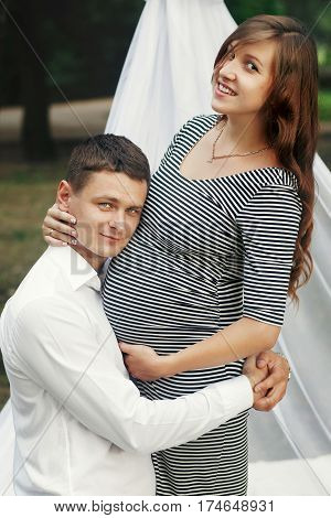 Happy Romantic Family Portrait, Husband Kneeling And Hugging Beautiful Pregnant Wife, Waiting For Ba
