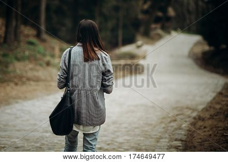 Beautiful hipster girl with black leather purse walking down pavement road in the countryside young woman tourist in stylish jacket looking down the path travel concept