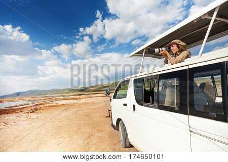 Young woman standing in open roof of safari minibus and taking pictures of African savannah