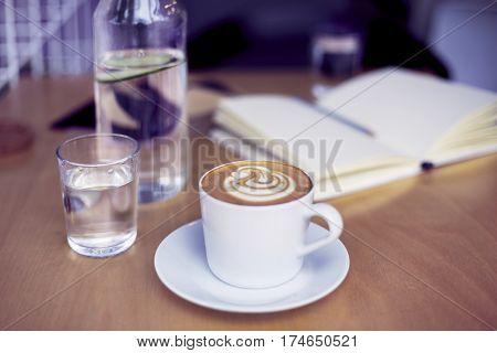 Cup of coffee cappucino glass of pure water bottle on wooden table bright interior daylight