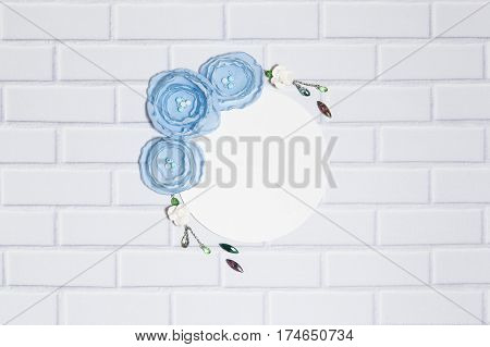 White Background With Handmade Garland With Gentle Blue Ranunculus Flowers, Roses and Crystals, Lying Flat on the White Brick Wall, Top View. Have a Empty Circle Place For Your Text.
