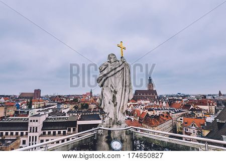 Wroclaw, Silesia, Poland - September, 18th, 2016. Wroclaw Old town high view from above the roof of Wroclaw university building and ancient stone statue with cross.