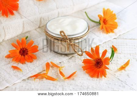Skincare cream in container tied with string, bright orange calendula holistic flowers scatted, white bathroom towel.