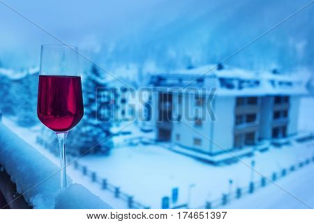 A glass of cold red wine on the snow-cowered balcony balustrade of hotel suite in winter season