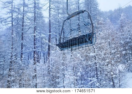 Empty cabin of chairlift high in the mountains against snow-covered winter forest
