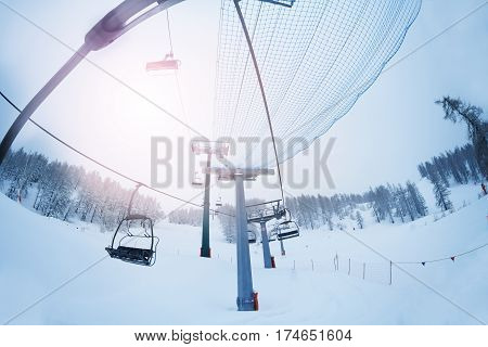 Aerial ropeway with empty chairlifts at mountain ski resort at foggy day