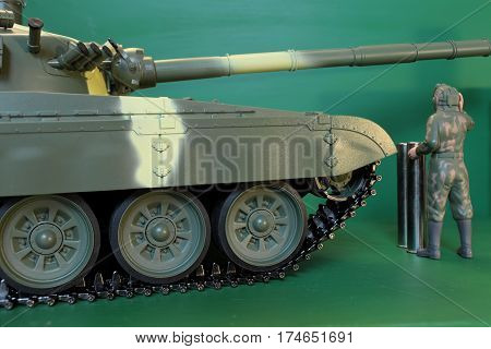 soldier in overalls and a helmet standing at battle tank