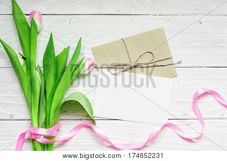 blank white greeting card and envelope with pink tulips over white wooden background. top view. mock up