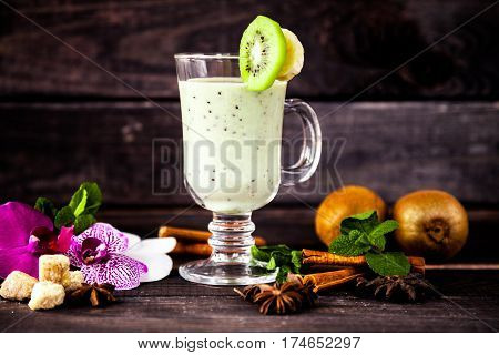 Сlear glass of organic fresh homemade kiwi and banana smoothie on a wooden background. Healthy lifestyle drink for breakfast, lunch. Vegetarian and diet dish.