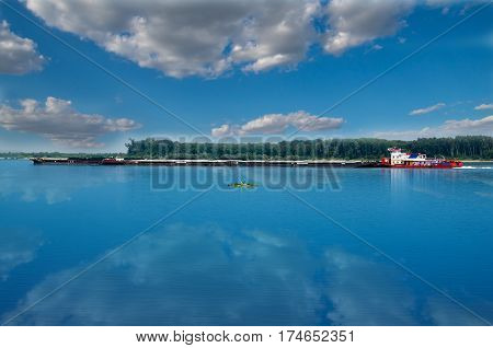 River Transport. Cargo ship with containers on the Danube river, Europe. Goods transport. European river shipping. Cargo boat on danube river.