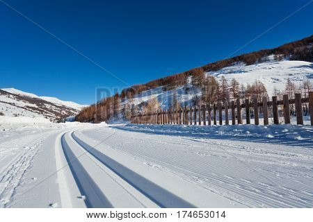 Beautiful picture of snowcapped road to alpine resort with ski tracks at frosty day