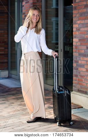 Full length portrait of young blonde woman in white blouse talking by cellphone standing outside near bricked building entrance with suitcase on wheels smiling and looking away