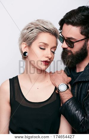 vertical portrait of fashion couple in love in stylish black clothes, wearing leather rock n roll look