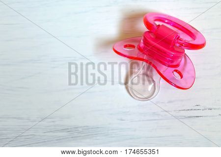 Pink baby soother on white grunge background