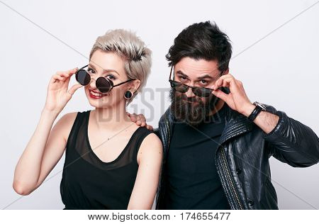 fashion couple in black clothes wearing black glasses and posing over white background. Hipster young bearded man and trendy blond woman looking at camera