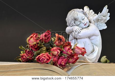 Bunch of wilted roses and angel sleeping on old book
