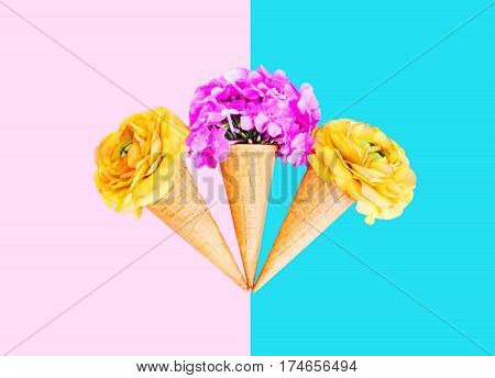 Three Ice Cream Cone With Colorful Flowers Over Pink Blue Background Top View