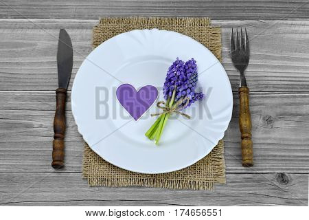 Decorated plate and silverware on wooden table