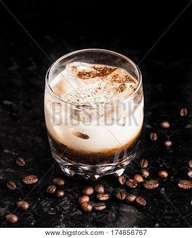 White russian cocktail with coffee beans on a marble table