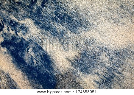 Black volcanic sand on the beach with a quaint pattern texture and background. Indonesia Bali