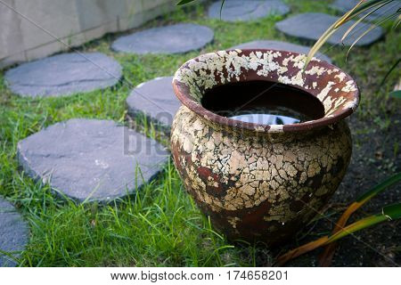Old textured clay vase with rainwater in the courtyard of the garden near the path of stones.
